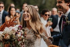 Bride at romantic outdoor fall ceremony holding a modern September bridal bouquet of garden roses, hanging amaranth, sweet peas, dahlias, cosmos and zinnias by Nectar and Root, Vermont wedding florist at Edson Hill in Stowe, Vermont.
