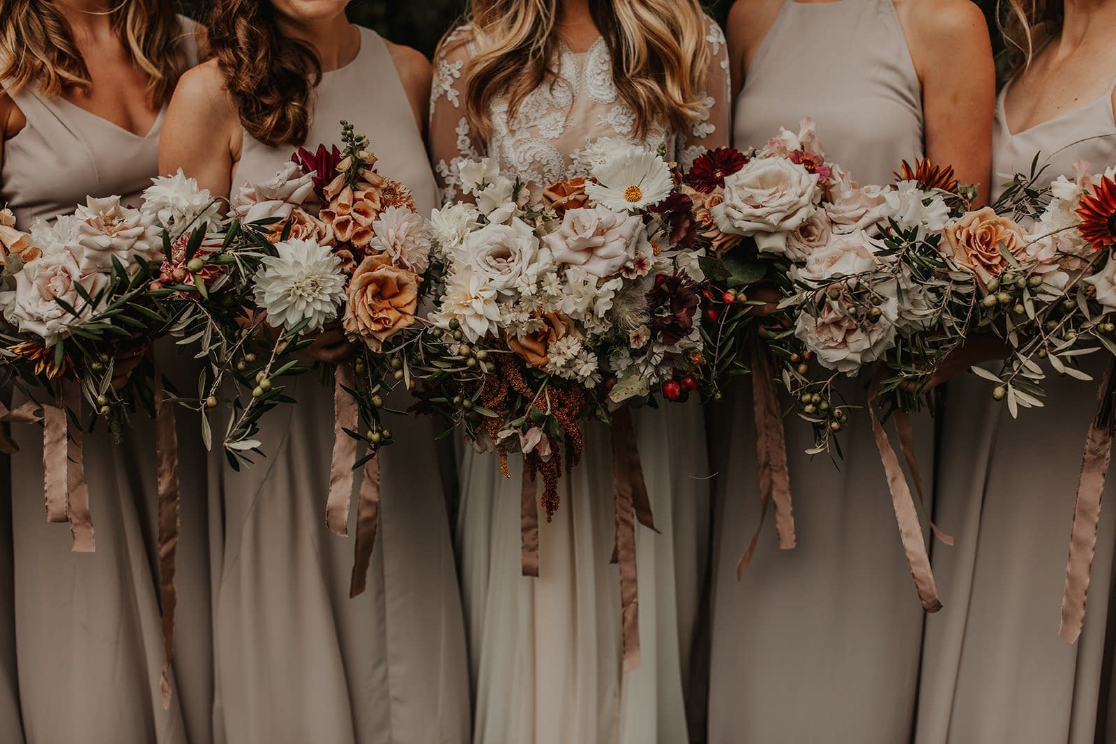 Bride and bridesmaids holding fall bouquets of garden roses, cosmos, and dahlias with flowing hand dyed silk ribbons in Stowe by Nectar and Root, Vermont wedding florist.