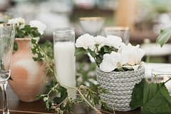 A lush summer reception centerpiece of vines and candles with June green and white garden roses in terracotta vases by Nectar and Root, Vermont wedding florist.