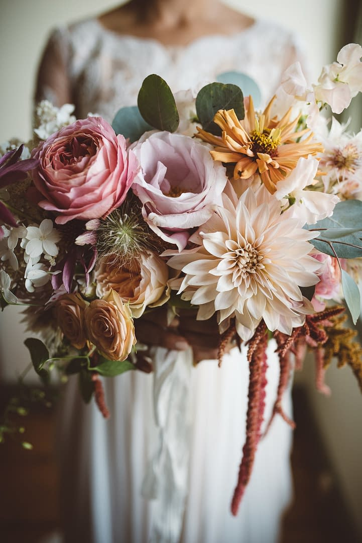 A lush summer bridal bouquet of September cafe au lait dahlias, eucalyptus, hanging amaranth and garden roses in a pastel color palette by Nectar and Root, a Vermont wedding florist.