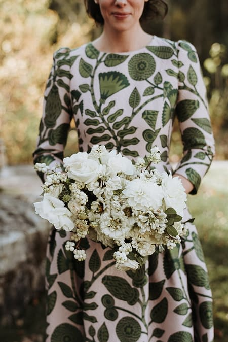 A micro wedding bride in a floral dress holding a green and white modern bridal bouquet of zinnias, garden roses, and berries designed by Nectar and Root, Vermont wedding florist at the Marble House Project in Dorset, Vermont.