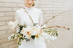 A bride wearing a short mock neck wedding dress holding an artful spring bridal bouquet of May tulips, garden roses, sweet peas, and flowering branches in a warm dusty neutral color palette by Nectar and Root, Vermont wedding florist.
