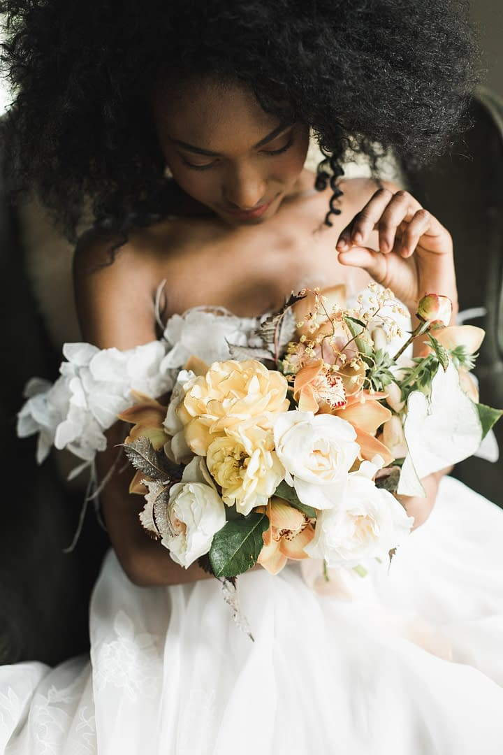 A simple spring peach, blush, yellow, and rust June bridal bouquet of garden roses, foxglove and orchids by Nectar and Root, a Vermont wedding florist at Foxfire Mountain House in the Catskills, New York.