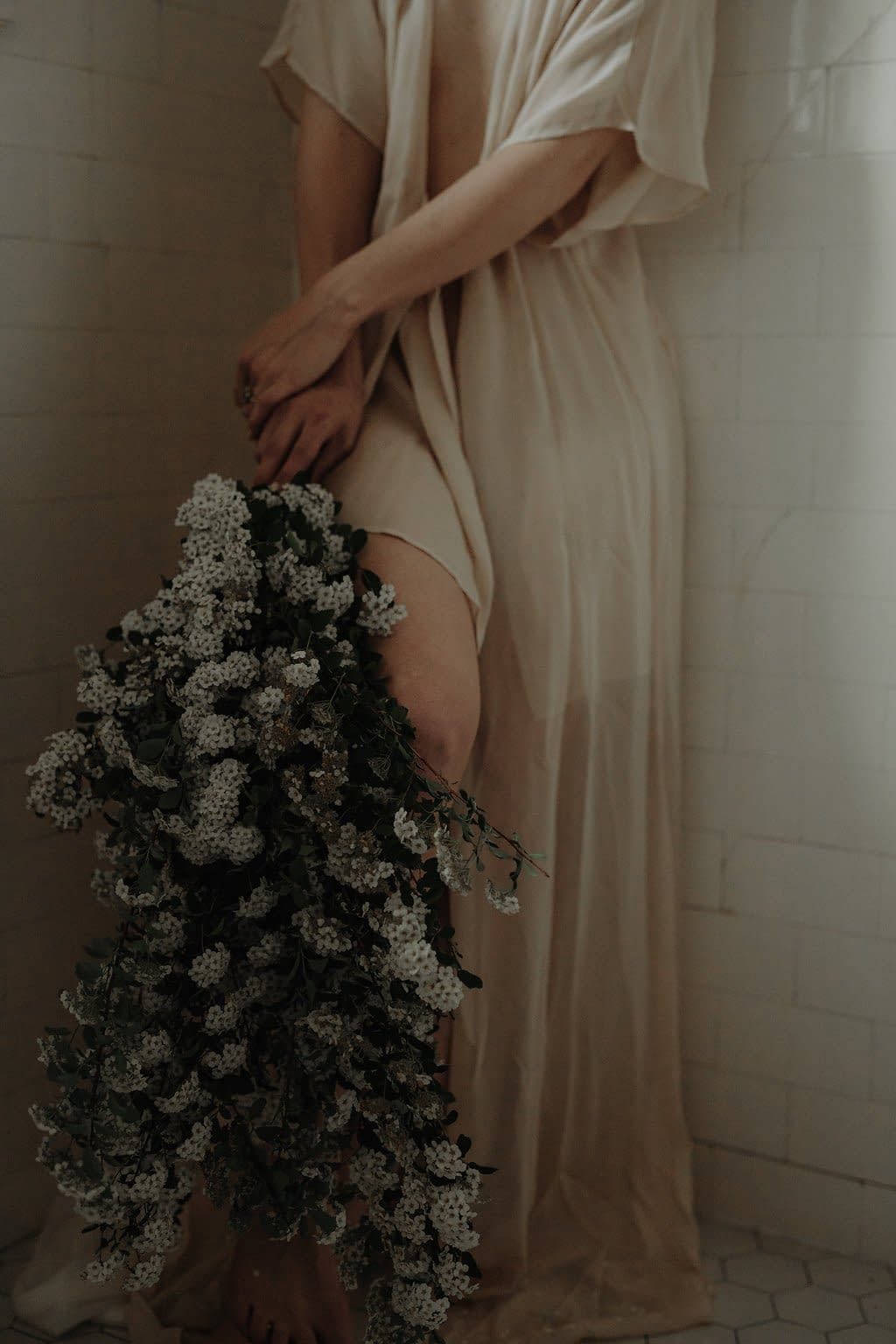 Intimate artful modern spring micro wedding bridal bouquet held by bride wearing lingerie featuring May flowering branches of spirea in green and white palette by Nectar and Root, Vermont wedding florist at the Inn at Shelburne Farms in Shelburne, Vermont.