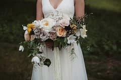 A lush summer bridal bouquet of June flowers in a moody color palette by Nectar and Root, Vermont wedding florist at West Mountain Inn in Arlington, Vermont.