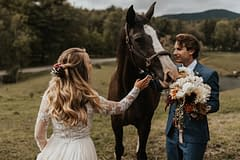 Bride and groom standing beside a horse at an outdoor fall private estate reception venue holding a modern bridal bouquet by Nectar and Root, Vermont wedding florist at Edson Hill in Stowe, Vermont.