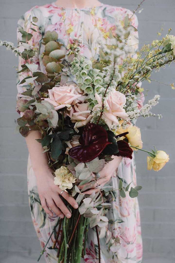 A bride wearing a floral dress holding a modern spring bridal bouquet of March fritillaria, flowering branches, eucalyptus, and garden roses in a pastel color palette by Nectar and Root, Vermont wedding florist in Brooklyn, New York.