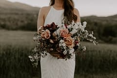 Outdoor micro wedding summer June bridal bouquet of peonies, belle epoque tulips, garden roses, iris, and flowering branches in warm desert neutral colors with flowing silk ribbon by Nectar and Root, Vermont wedding florist at a backyard wedding in Vermont.