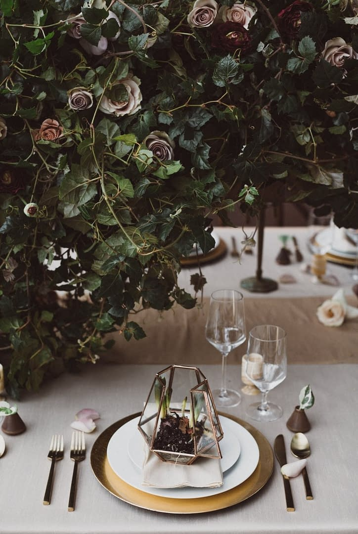 A modern winter reception centerpiece of February flowers in a moody color palette by Nectar and Root, Vermont wedding florist at Trapp Family Lodge in Stowe, Vermont.