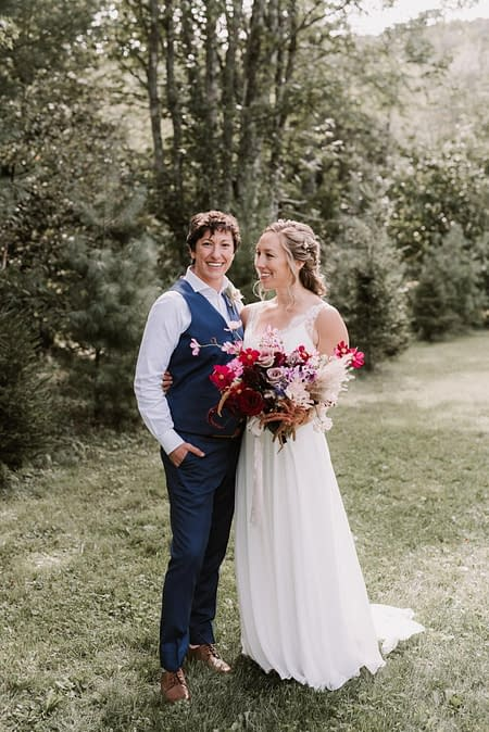A beautiful same sex couple standing together outside embracing after their ceremony, holding an artful bridal bouquet with dried pampas grass designed by Nectar and Root, Vermont wedding florist.