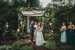 Fall micro wedding bride and groom standing outside under a rustic ceremony chuppah with September cafe au lait dahlias, garden roses, and eucalyptus in a peach, blush and green palette by Nectar and Root, Vermont wedding florist at Foxfire Mountain House in Catskills, New York.