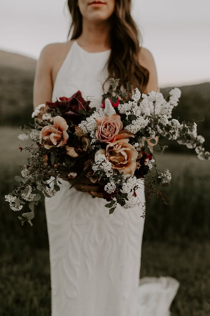A boho peach, blush and burgundy June bridal bouquet of peonies, belle epoque tulips, garden roses, iris, and flowering branches with flowing silk ribbon by Nectar and Root, a Vermont wedding florist at a backyard micro wedding in Vermont.