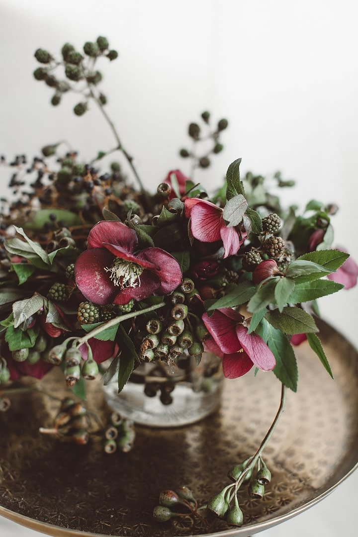 A modern spring reception centerpiece in a moody dark color palette atop a metal table table with a clear glass vase featuring eucalyptus and hellebores by Nectar and Root, Vermont wedding florist.