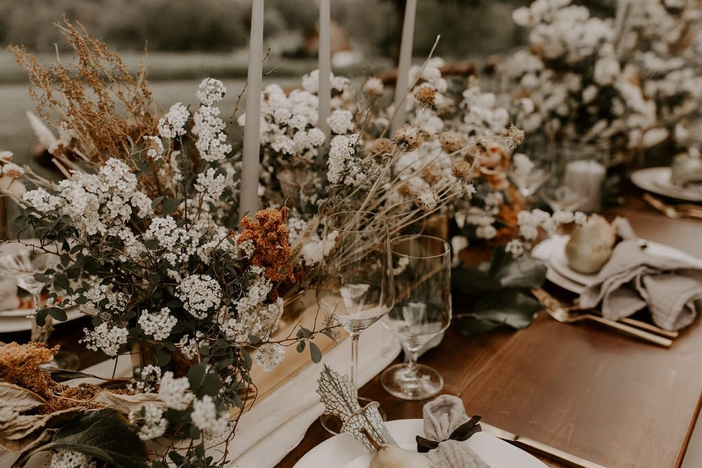 A boho outdoor reception centerpiece of dried flowers, dried grasses, tapered candles and flowering branches in a gold vase on a wooden table for a micro wedding designed by Nectar and Root, Vermont wedding florist.