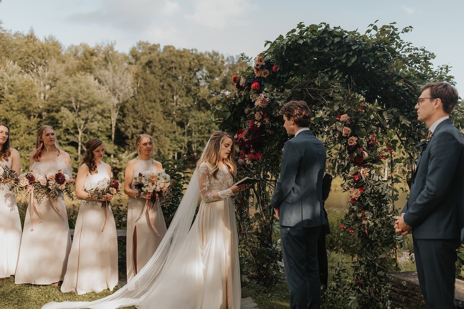 Bride and groom standing beside romantic outdoor fall ceremony arbor while holding a modern September bridal bouquet of garden roses, hanging amaranth, sweet peas, dahlias, cosmos and zinnias by Nectar and Root, Vermont wedding florist at Edson Hill in Stowe, Vermont.