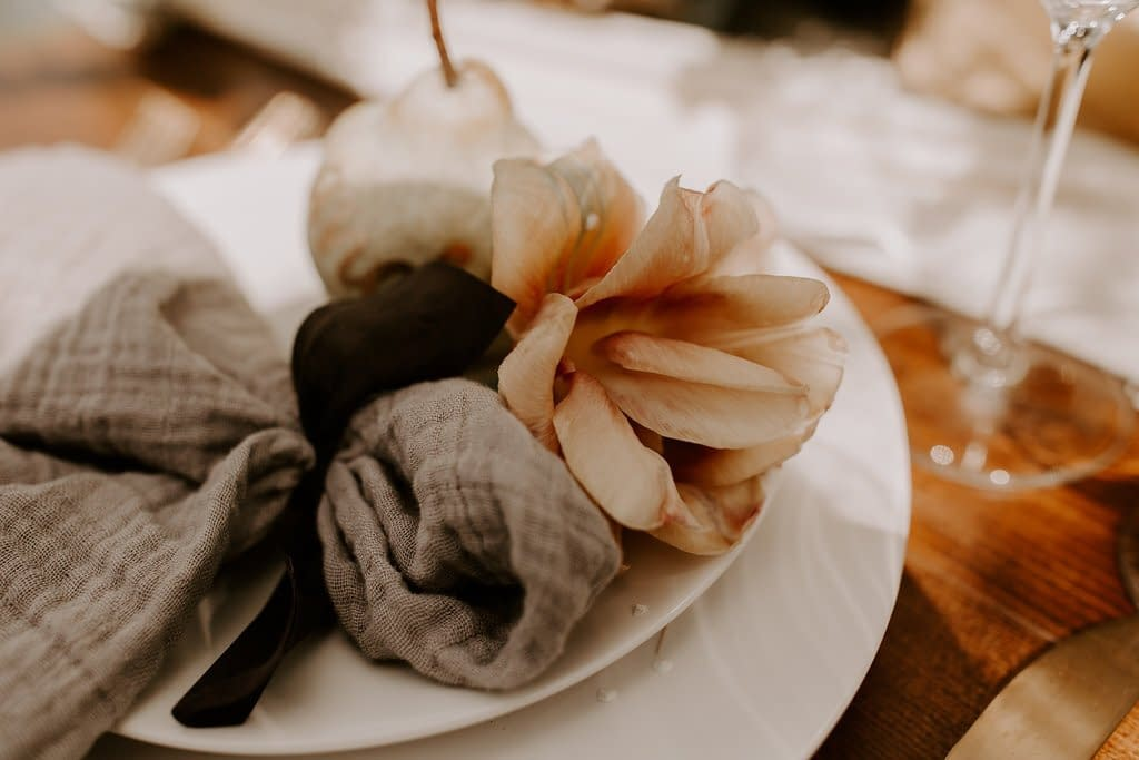 Artful napkin accent and place setting made of a hand dyed silk ribbon, cheesecloth napkin, belle epoque tulip and anjou pear in warm neutral tones for outdoor micro wedding by Nectar and Root, Vermont wedding florist at a backyard wedding in Vermont.