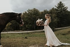Bride standing beside a horse at an outdoor fall private estate reception venue holding a modern bridal bouquet by Nectar and Root, Vermont wedding florist at Edson Hill in Stowe, Vermont.