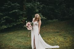 Fall micro wedding bride holding a peach modern bridal bouquet of September cafe au lait dahlias and garden roses by Nectar and Root, Vermont wedding florist at Foxfire Mountain House in Catskills, New York.