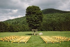 A lush summer ceremony space of July flowers in a neutral color palette by Nectar and Root, Vermont wedding Florist at Riverside Farm in Pittsfield, Vermont.