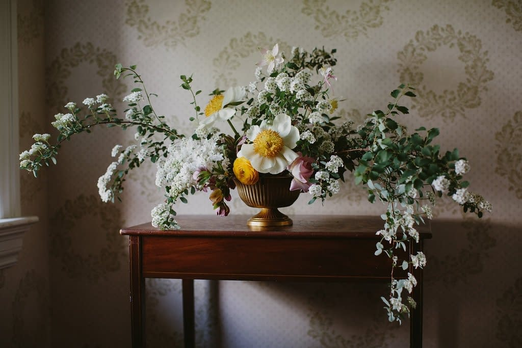A simple spring reception centerpiece in a yellow color palette and gold vase atop a wooden table with wallpaper featuring peonies, ranunculus, garden roses and flowering branches by Nectar and Root, Vermont wedding florist.