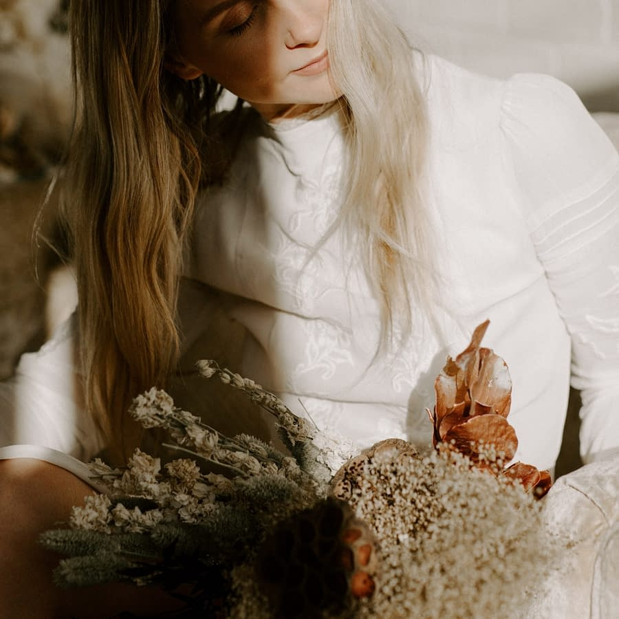 A bride holding a modern bridal fall bridal bouquet of dried flowers in a warm dusty neutral color palette in the sunshine by Nectar and Root, Vermont wedding florist.