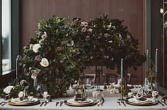 A lush winter reception centerpiece of February flowers in a moody color palette by Nectar and Root, Vermont wedding florist at Trapp Family Lodge in Stowe, Vermont.