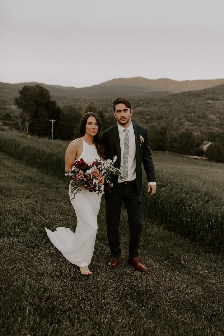 Outdoor elopement bride and groom with mountain views holding a peach, blush and burgundy bridal bouquet by Nectar and Root, Vermont wedding florist at a backyard wedding in Vermont.