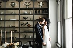 Bride and groom embracing next to centerpiece by Nectar and Root, Vermont wedding florist at Foxfire Mountain House in the Catskills, New York.