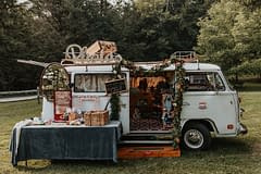Vintage photo booth bus decorated with fall hanging garland installation of September foliage by Nectar and Root, Vermont wedding florist at Edson Hill in Stowe, Vermont.