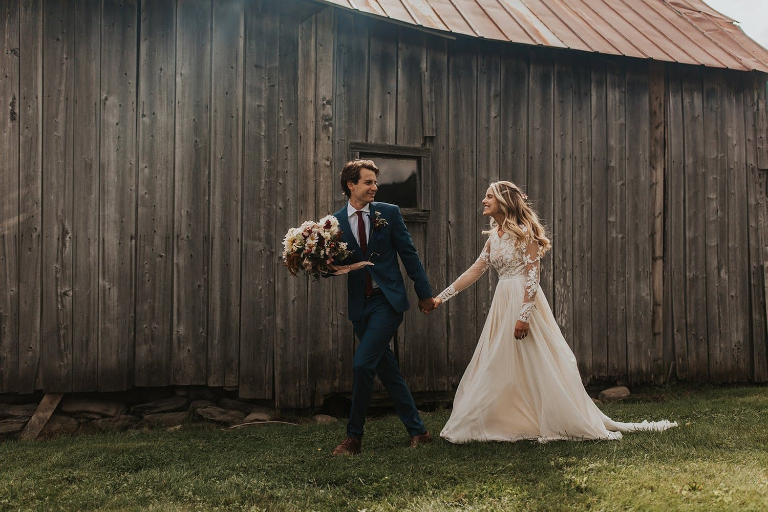 Bride and groom at romantic outdoor fall barn holding a modern September bridal bouquet of garden roses, hanging amaranth, sweet peas, dahlias, cosmos and zinnias by Nectar and Root, Vermont wedding florist at Edson Hill in Stowe, Vermont.