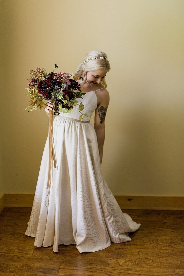 A boho bride wearing a beaded white wedding dress holding a fall bridal bouquet of September dahlias, hydrangea, and fall foliage in a burgundy and blush color palette with flowing hand dyed silk ribbons by Nectar and Root, Vermont wedding florist