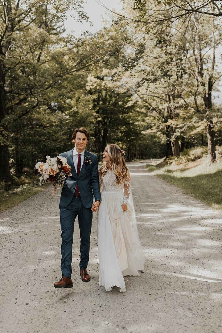 Bride and groom at romantic outdoor fall private estate holding a modern September bridal bouquet of garden roses, hanging amaranth, sweet peas, dahlias, cosmos and zinnias by Nectar and Root, Vermont wedding florist at Edson Hill in Stowe, Vermont.