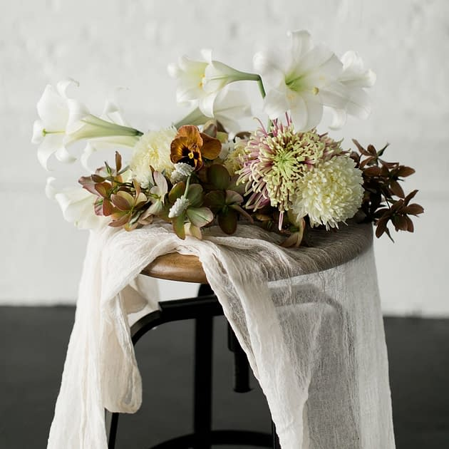 A modern spring reception centerpiece in a warm neutral palette atop an industrial table with cheesecloth tablecloth featuring lilies, pansies, mums and hellebores by Nectar and Root, Vermont wedding florist.