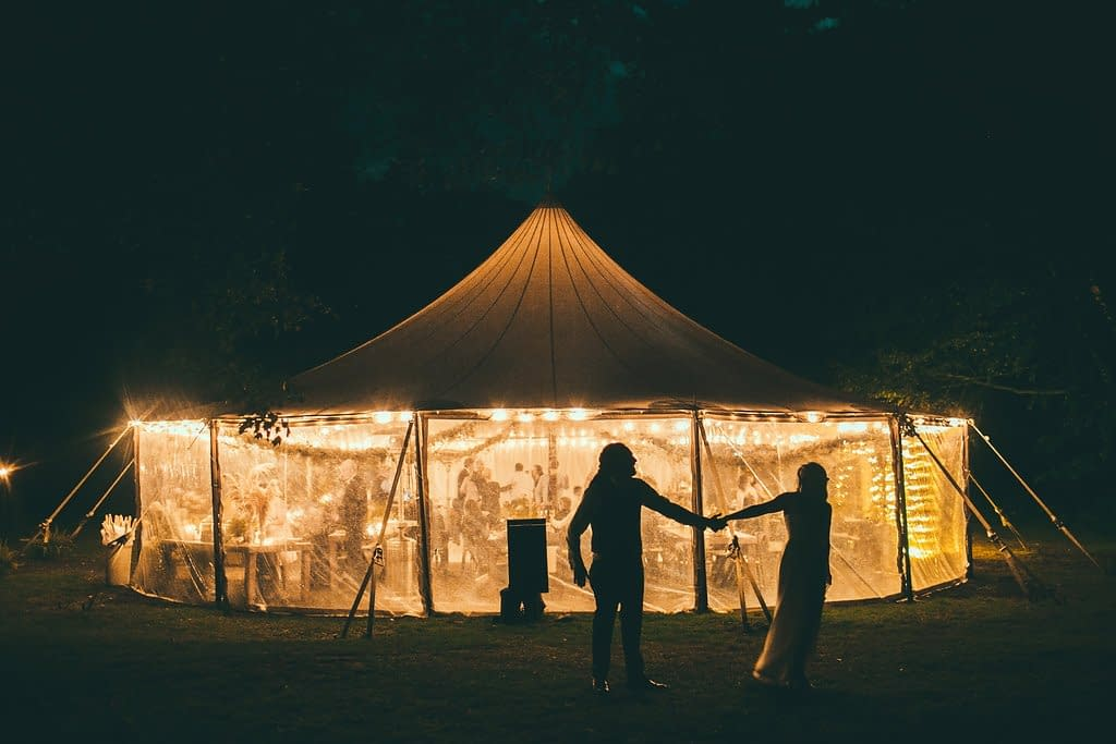 Bride and groom standing outside of outdoor micro wedding tented reception with details by Nectar and Root, Vermont wedding florist at Foxfire Mountain House in Catskills, New York.