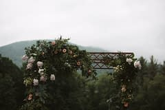 A simple summer arbor of June flowers in a moody color palette by Nectar and Root, Vermont wedding florist at West Mountain Inn in Arlington, Vermont.