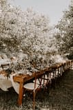 Outdoor boho summer farm table micro wedding reception centerpiece runner of greenery, dried flowers, and other June summer flowers by Nectar and Root, Vermont wedding florist at a backyard wedding in Vermont.