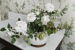 A simple summer reception centerpiece in a green and white neutral color palette atop a marble table with a marble vase featuring garden roses by Nectar and Root, Vermont wedding florist at Shelburne Museum in Shelburne, Vermont.