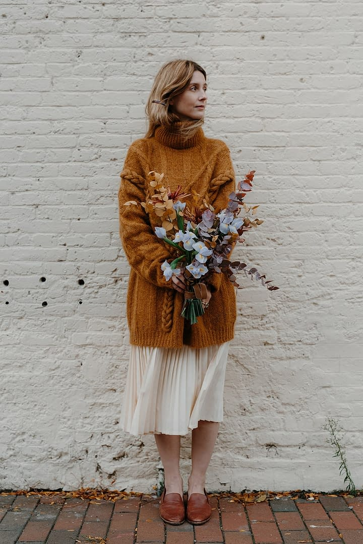 A bride standing outside holding a romantic fall bridal bouquet of October eucalyptus, mums, iris and hellebores in a moody blue color palette by Nectar and Root, Vermont wedding florist.