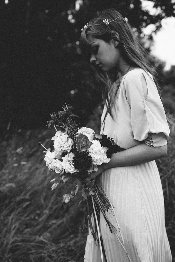 A boho wildflower bridesmaids bouquet held by a bridesmaid at an outdoor ceremony by Nectar and Root, Vermont wedding florist in Burlington, Vermont.
