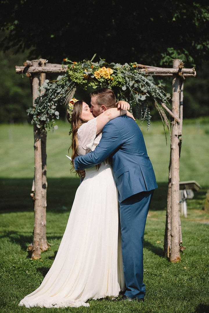 A boho summer arbor of July flowers in a neutral color palette by Nectar and Root, Vermont wedding Florist at Riverside Farm in Pittsfield, Vermont.