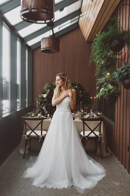 A bride standing in front of a lush indoor reception centerpiece designed by Nectar and Root, Vermont wedding florist at Trapp Family Lodge in Stowe, Vermont.