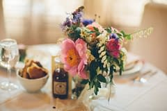 A lush summer reception centerpiece of June flowers in a neutral color palette by Nectar and Root, Vermont wedding florist at Alerin Barn in Saint Johnsbury, Vermont.