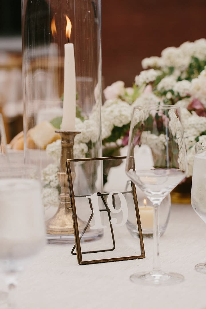 White centerpiece next to tapered candlesticks, gold candleholders and gold table number by Nectar and Root, Vermont wedding florist at Shelburne Coach Barn in Shelburne, Vermont.