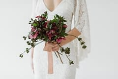 A bride in a rue de seine wedding dress holding a simple modern purple bridal bouquet of spring May hellebores with flowing hand dyed silk ribbon by Nectar and Root, Vermont wedding florist.