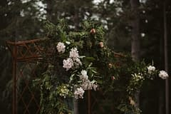 A lush summer arbor of June flowers in a moody color palette by Nectar and Root, Vermont wedding florist at West Mountain Inn in Arlington, Vermont.