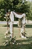 A lush fall floral arbor of September flowers in a neutral color palette by Nectar and Root, Vermont wedding florist at Coach Barn at Shelburne Farms in Shelburne, Vermont.