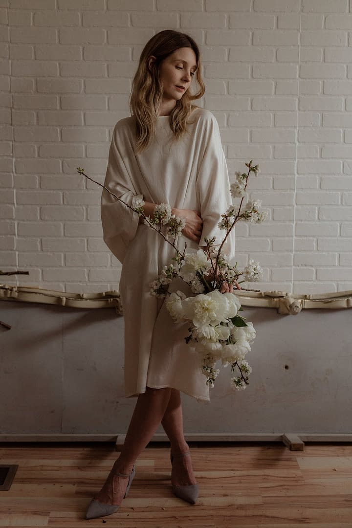 A bride standing inside wearing a simple modern silk wedding dress holding a spring bridal bouquet of May white flowering branches by Nectar and Root, Vermont wedding florist.