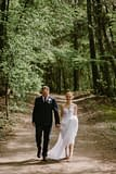 Bride and groom walking through trees by Nectar and Root, Vermont wedding florist at Shelburne Coach Barn in Shelburne, Vermont.