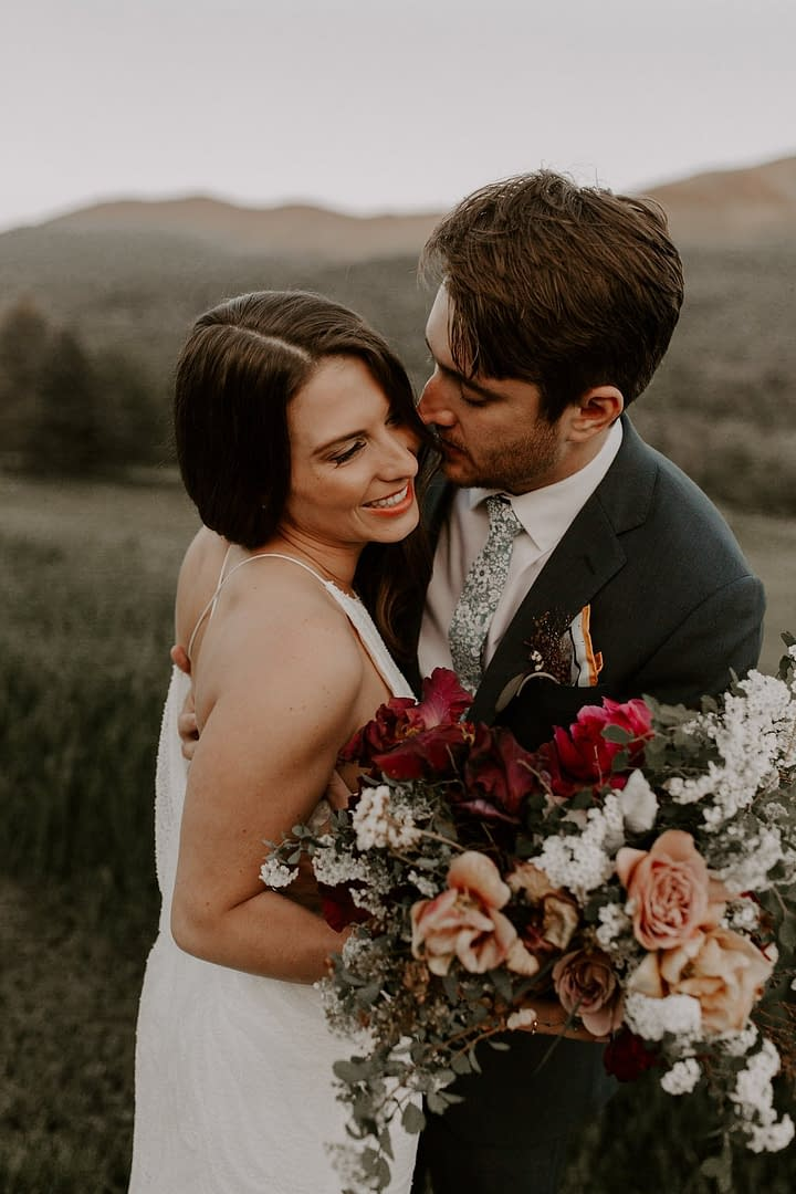 Outdoor micro wedding bride and groom with mountain views holding a summer bridal bouquet by Nectar and Root, Vermont wedding florist at a backyard wedding in Vermont.