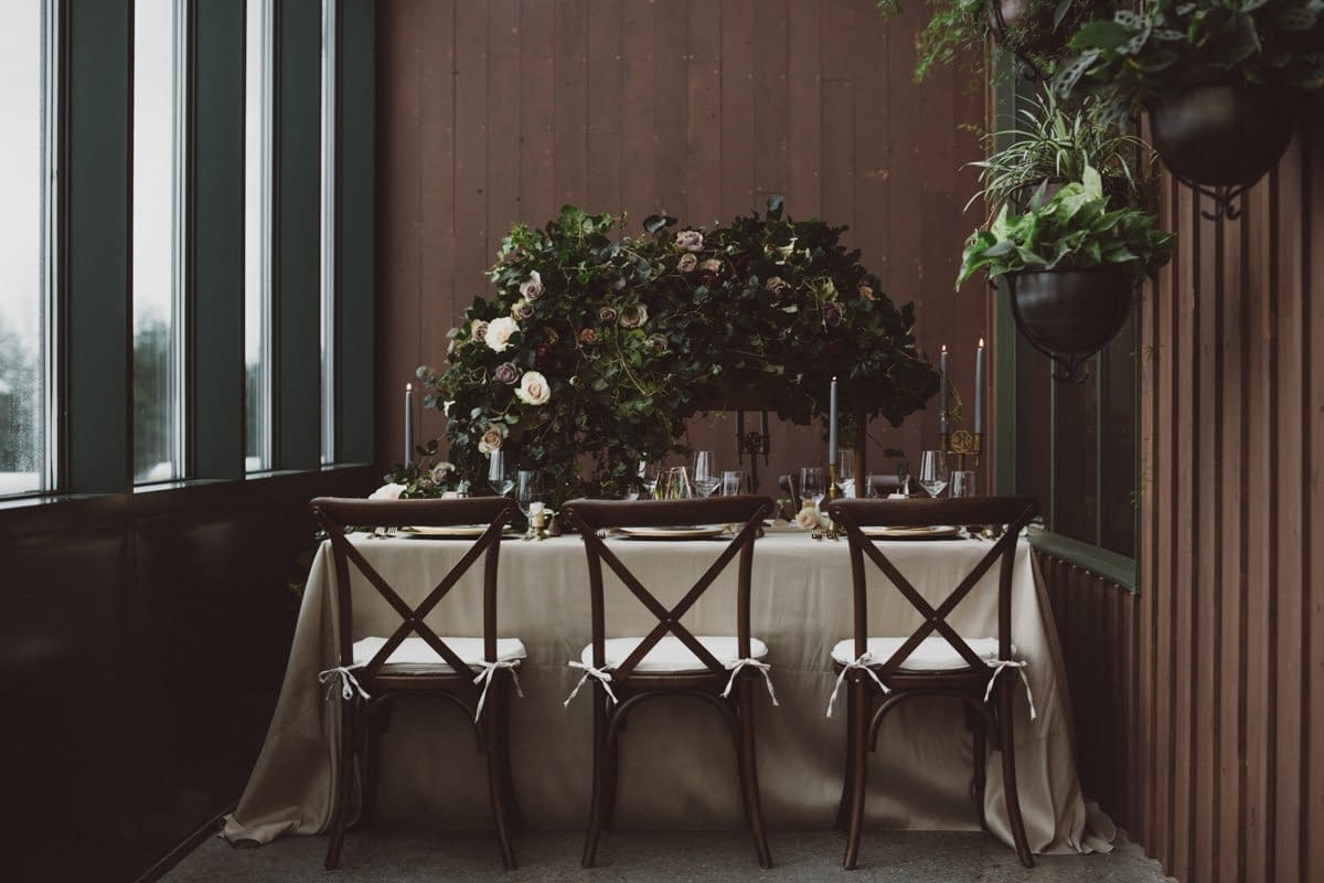 A simple winter reception centerpiece of February flowers in a moody color palette by Nectar and Root, Vermont wedding florist at Trapp Family Lodge in Stowe, Vermont.